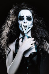 Young woman in the image of sad gothic freak clown with scissors
