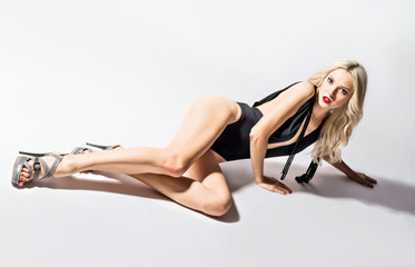 Studio fashion shot: a sexy young woman in swimsuit lying on the floor