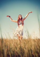 Beautiful young hippie girl dancing in the field at sunset time