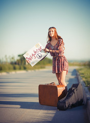 Portrait of beautiful young hippie woman hitchhiking on a road