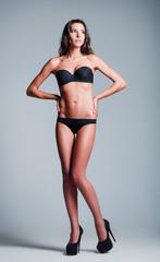 Studio fashion shot: beautiful young girl wearing black lingerie and shoes