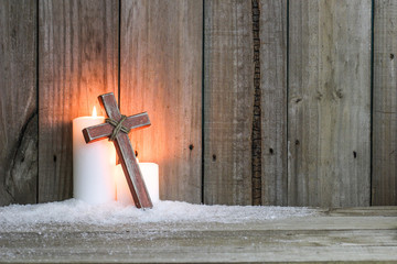 White candles glowing behind wood cross