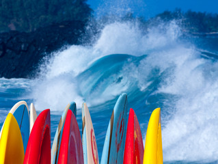 Powerful waves break at Lumahai Beach, Kauai with Surfboards