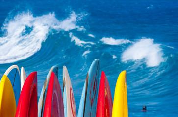 Powerful waves break at Lumahai Beach, Kauai with Surfboards