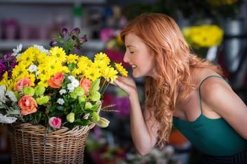 Female florist smelling flower