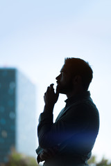 silhouette of an attractive young businessman thinking in front of a skyscraper, graded with a lens flare