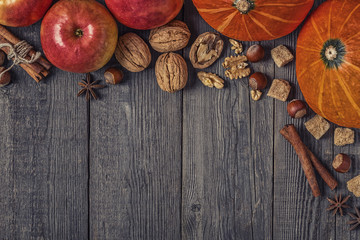 Wooden background with pumpkin, apples, nuts and spices.