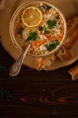 Chicken soup with pasta on a dark wooden background.