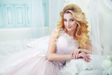 Portrait of a beautiful blonde bride with elegant curls on the bed in the boudoir.