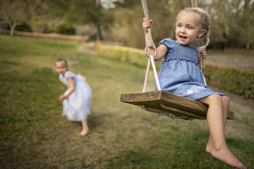 Two happy sisters playing on a swing in the garden.