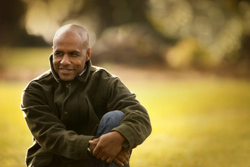 Smiling mid adult man sitting in a park.