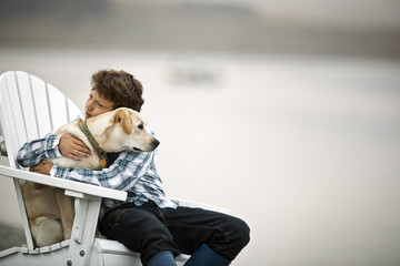 Boy sitting on outdoor chair while hugging his dog at the beach.