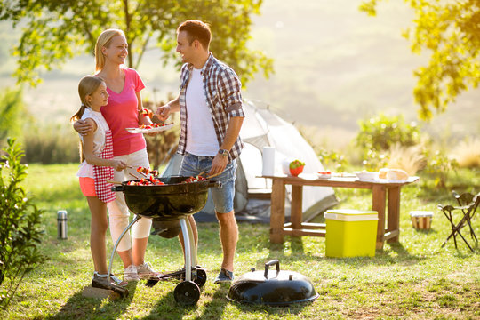 smiling parent grilling meat with daughter.