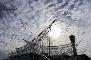 雲間から透ける陽光と屋根のシルエット