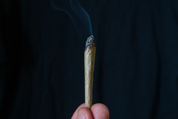marijuana or cannabis joint smoking isolated against a black background