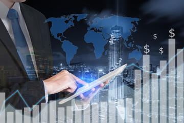 Double exposure of businessman using the tablet with city