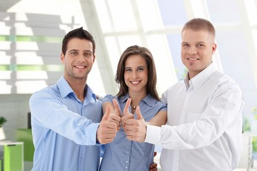Successful startup business team giving thumbs up