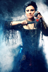 Halloween Witch creates magic. Attractive woman in witches costume with voodoo doll in hand
