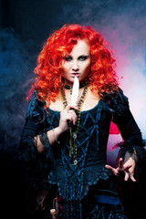 Halloween Witch creates magic. Attractive woman with red hair in witches costume