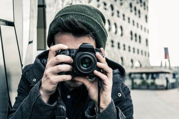 Ritratto di un uomo giovane e caucasico, mentre scatta una foto con la sua macchina fotografica, in vacanza.