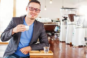 man enjoying his cup of coffee near coffee making machine