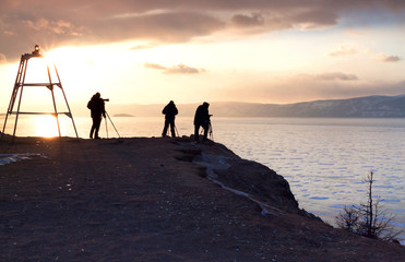 Photographers are taking photos at sunset time. people silhouette. Winter at Lake Baikal. Winter leisure