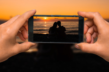 Taking photo of loving couple at sunset with mobile phone