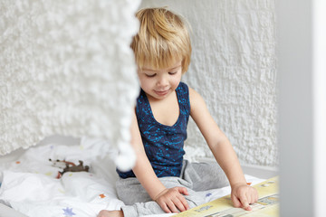 Childhood and leisure. Adorable sweet little blonde boy in sleeping suit sitting on his bed in front of open book, pointing his index finger, showing pictures, looking concentrated. Cozy scene