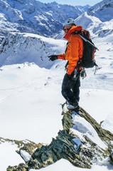 Alpinist steht auf einem schmalen Grat im Hochgebirge