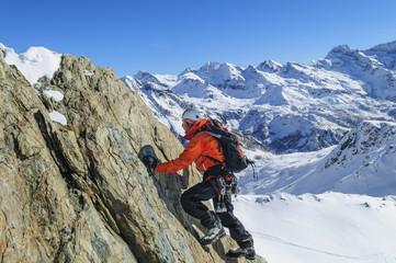 Alpinist klettert an einer Felswand im winterlichen Gebirge