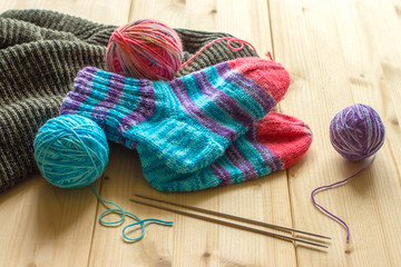 Handmade baby socks, multicolor skeins and knitting needles