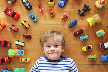 A young boy on a wood floor with all his cars and toys around him. Picture taken from above him, with a focus on his face and blurry toys