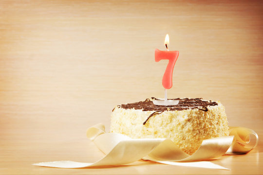 Birthday cake with burning candle as a number seven. Focus on the candle
