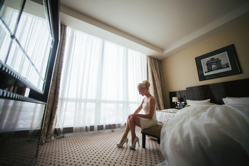 Elegant lady in white dress sits on a bench in a hotel room