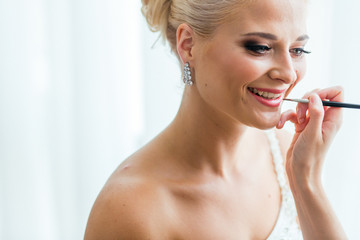 Delicate lady's hand adjust a lipstick on bride's smile with a t
