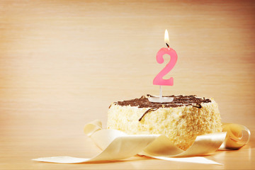Birthday cake with burning candle as a number two. Focus on the candle