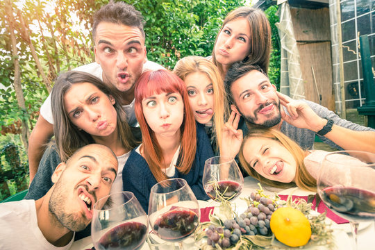 Best friends taking selfie outdoor with back lighting - Happy youth concept with young people having fun together drinking wine - Cheer and friendship at grape harvest time - Soft desaturated filter