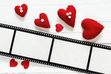 Background with a frame in the form of a film, and red hearts. S