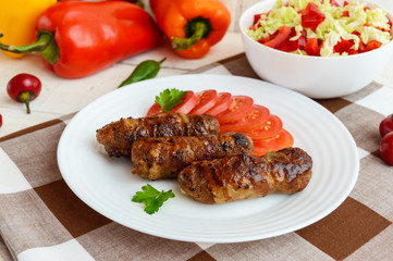 Juicy grilled rolls of minced meat wrapped in bacon with fresh tomato and a light salad of Chinese cabbage and bell pepper.
