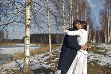 Brunette bride hugs groom tightly standing in the birch grove