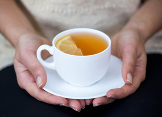 cup of tea with lemon in two hands