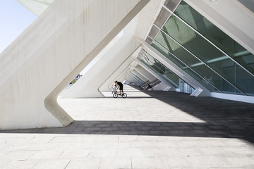 teenagers on BMX ride next to a modern building