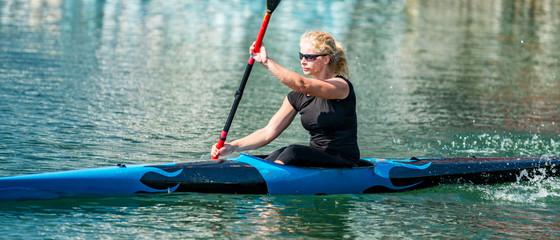 Sport kayak. Female kayaking champion paddling