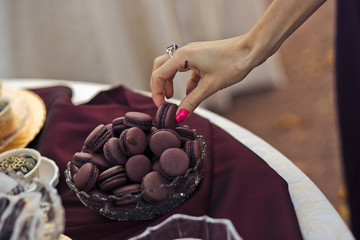 Guest is taking a purple macaroon on the wedding