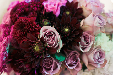 Nice bouquet with the purple roses on the wedding table