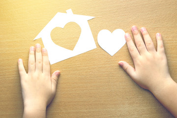 children hands with small model of house and heart on wooden bac