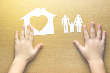 children hands with small model of house and family on wooden ba