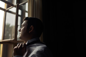 Brunette groom is standing next to the window