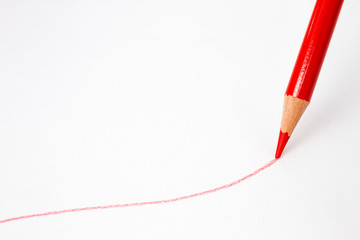 Red pencil drawing a line on a white paper