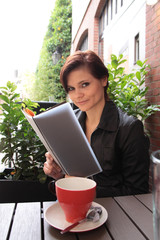 Frau im Café liest Speisekarte